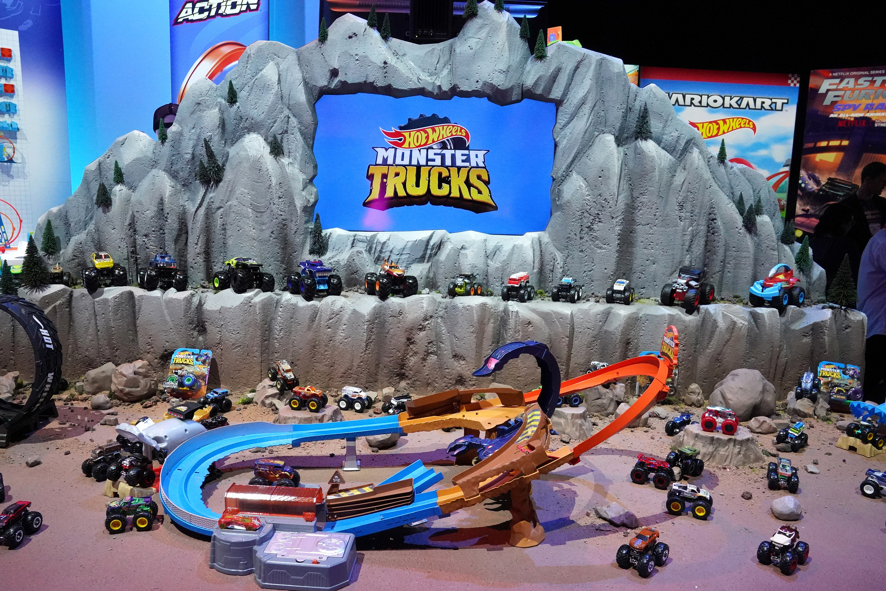 A display set up of Hot Wheels Monster Trucks, with trucks lined up against a toy cliff face, and a race track at the bottom, with my trucks surrounding it