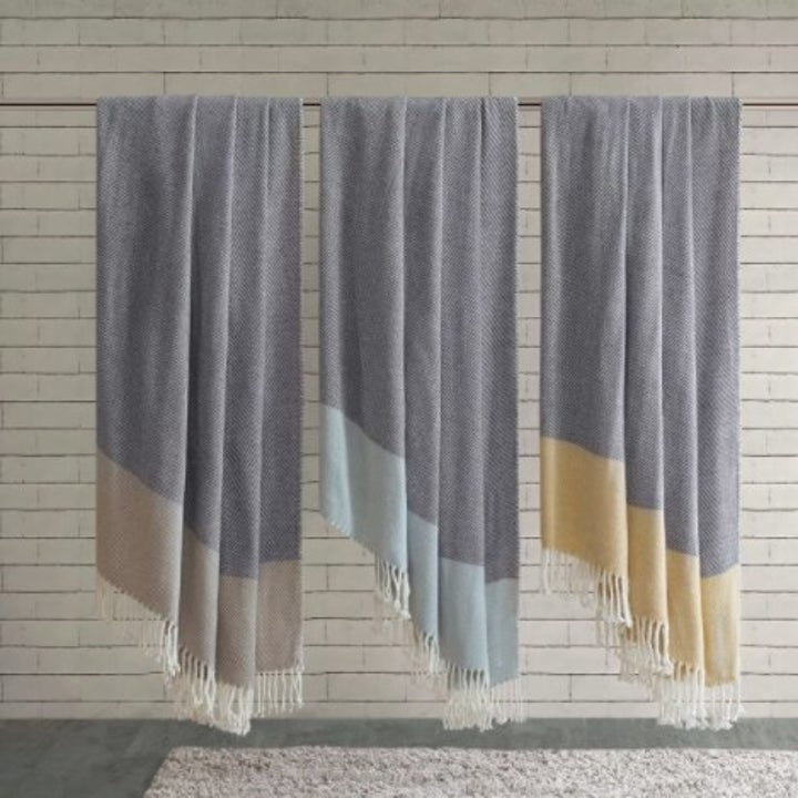 Three color block throws hanging side by side in blue, taupe brown, and yellow