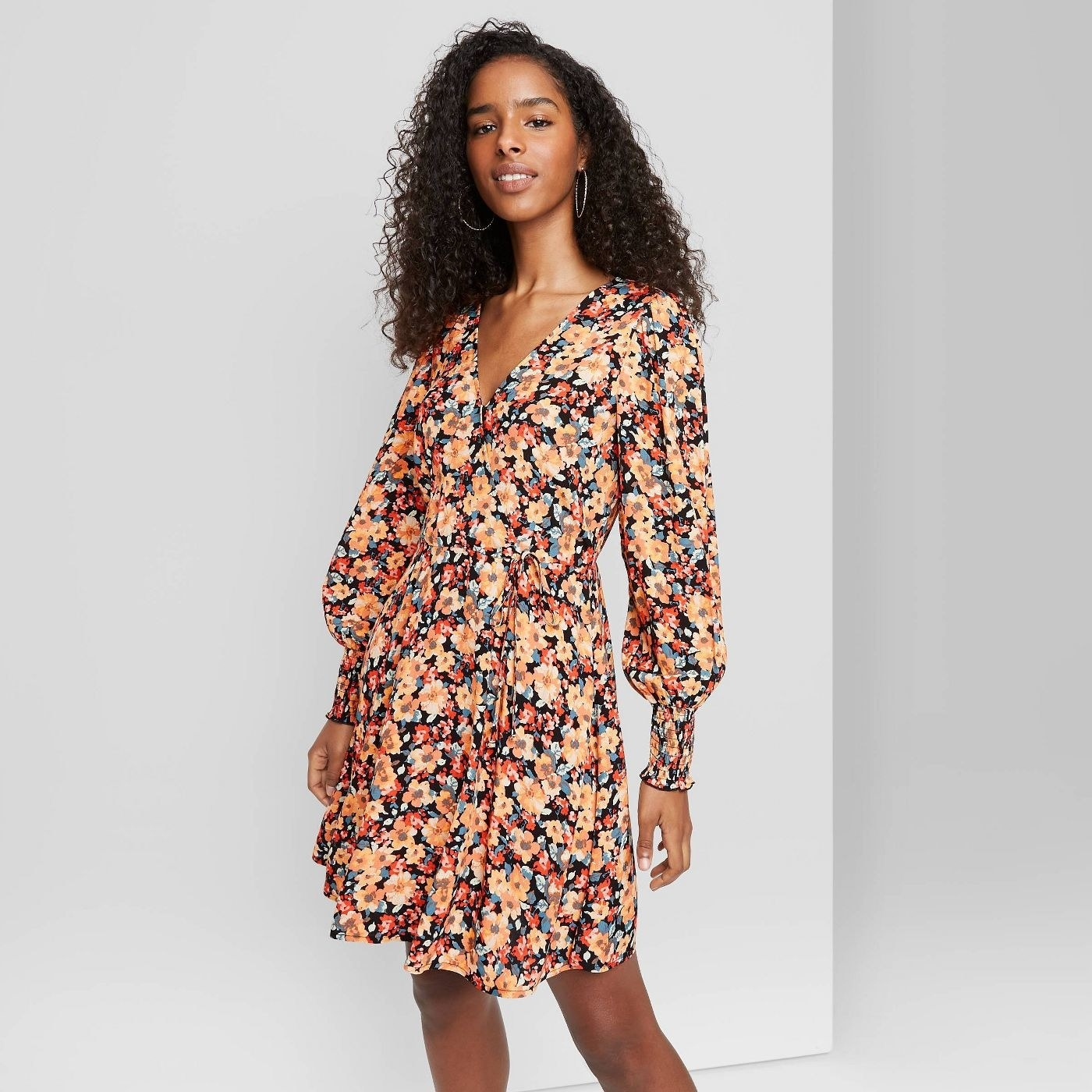 Model wearing floral mini dress with orange, red, and light blue flowers