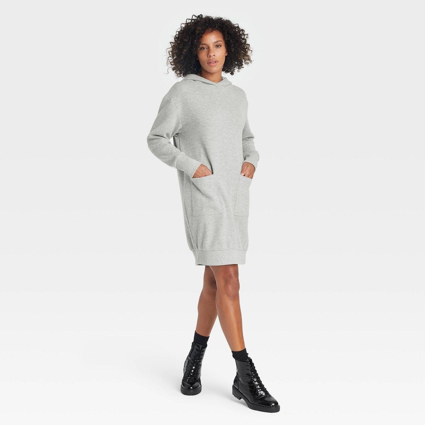 Model wearing a gray sweatshirt dress