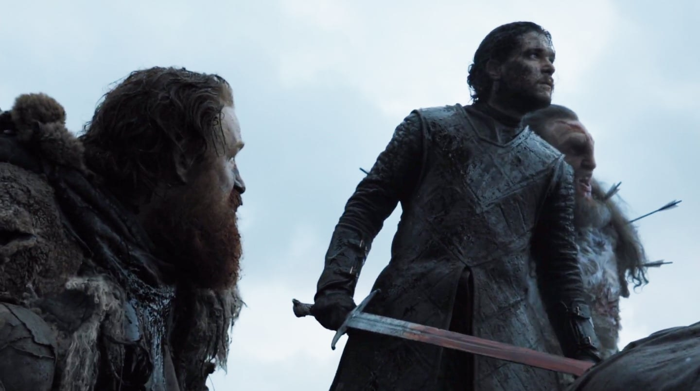 tormund looks up at jon snow who is holding a sword