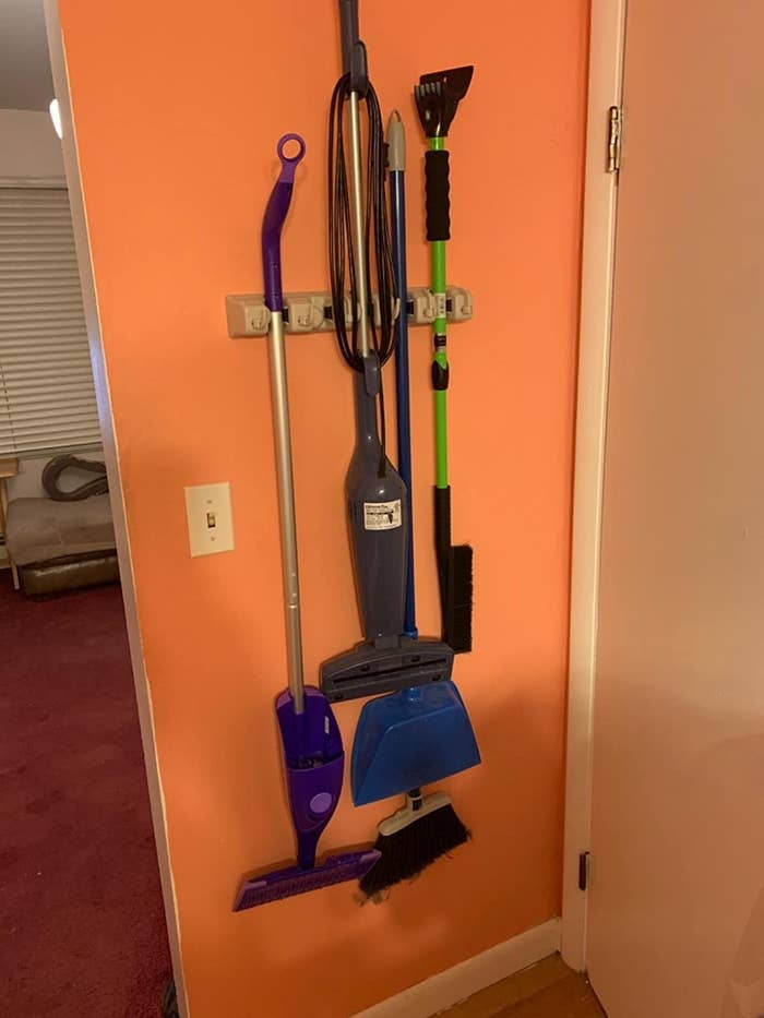 a reviewer photo of the mop and broom holder hanging against an orange wall that's holding a swifter wet jet mop a steamer two brooms and a dust pan