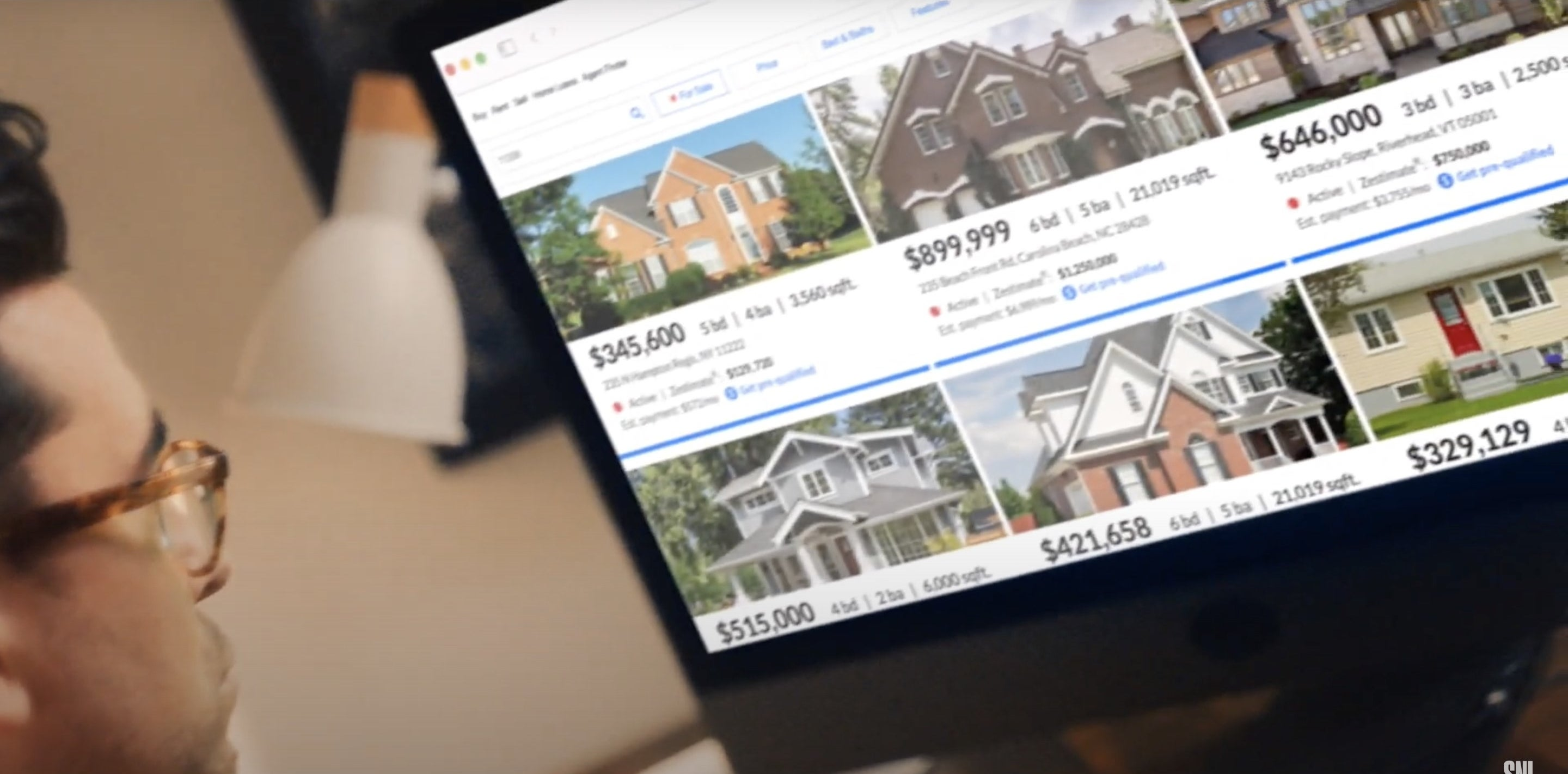 A man looks at a screen filled with Zillow listings