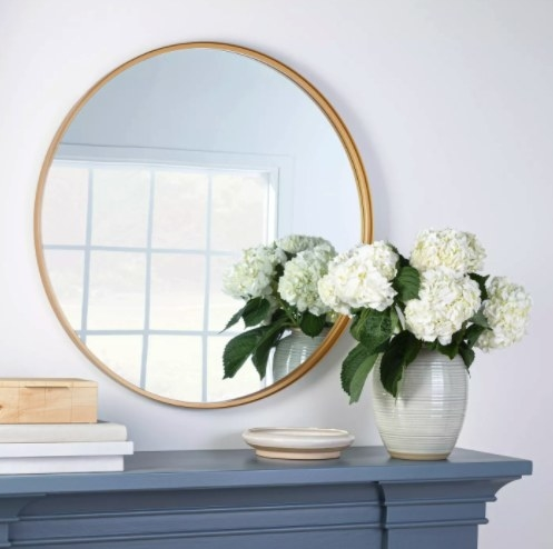 The mirror in the color brass above a fireplace