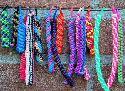 14 different scoobie bracelets hanging from a string against a brick wall, varying in colour and length