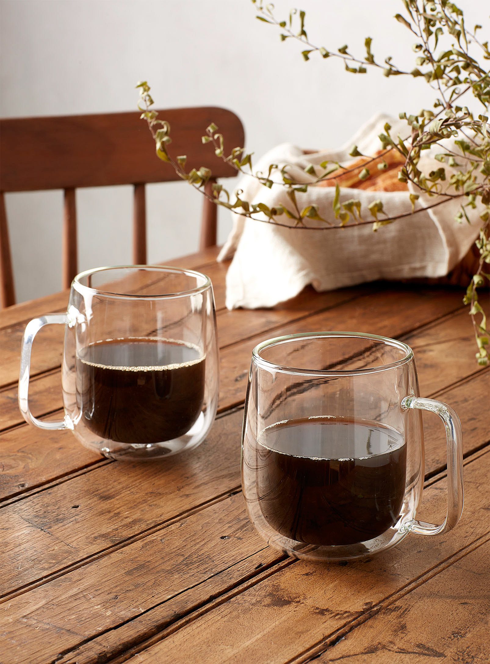 Two glass mugs of coffee on a wooden table