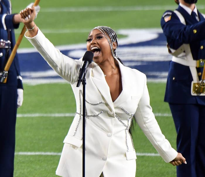 Jazmine lifts her hand in the air while singing in a stunning white suit