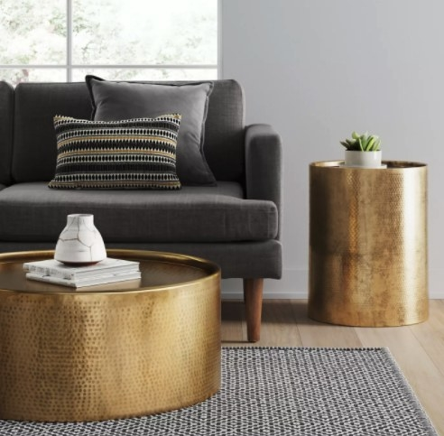 The gold drum style accent table in a living room