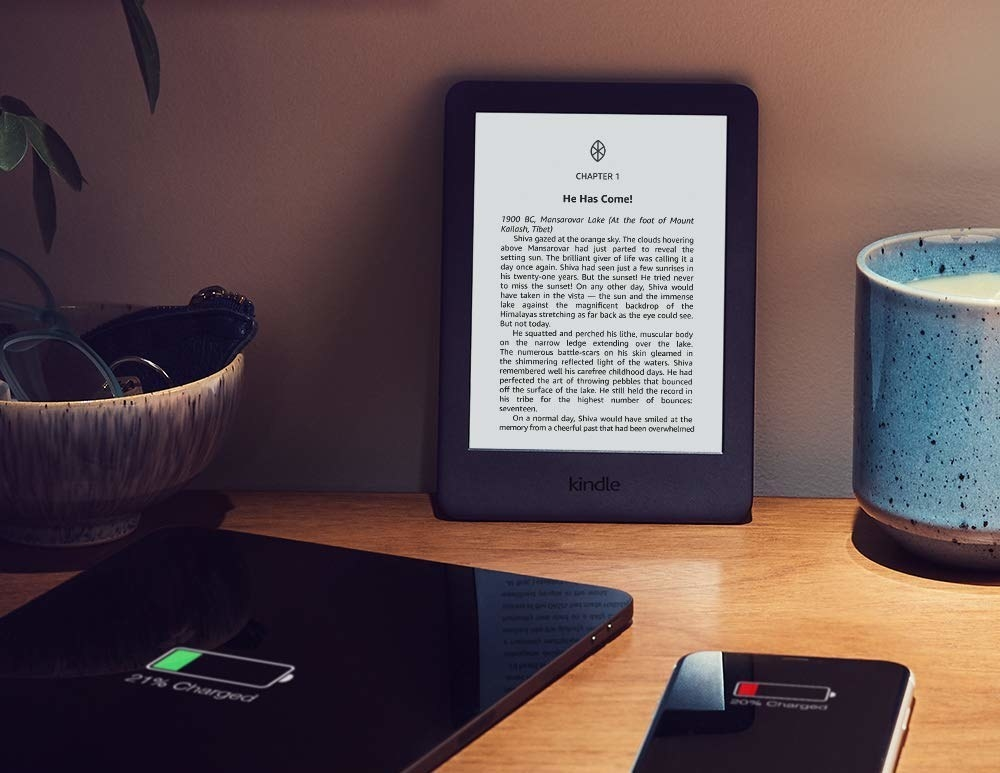An Amazon Kindle on a table next to a plant and other smart devices