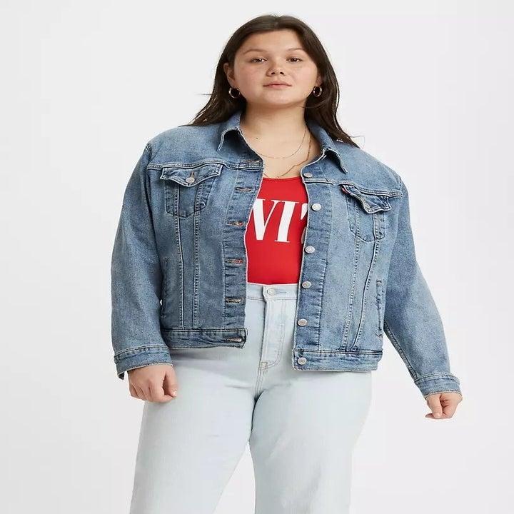 Model wears light blue Levi's Ex-Boyfriend Trucker Jacket with white straight high-rise jeans