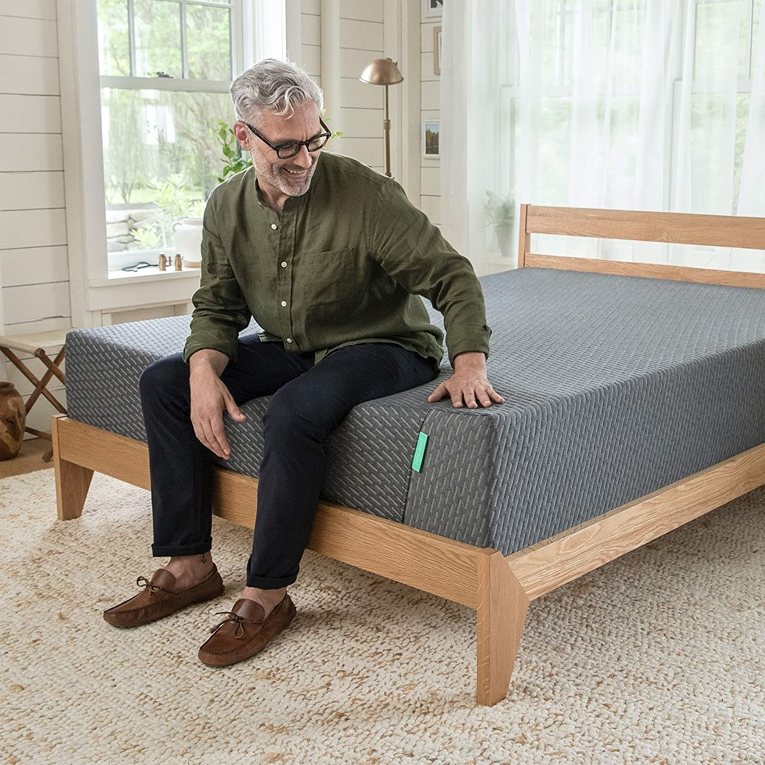 the mattress with a model sitting on it, showing how adaptive it is