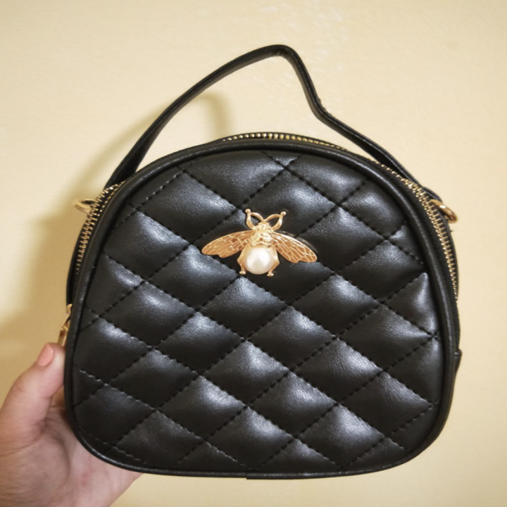 reviewer holding quilted black crossbody bag