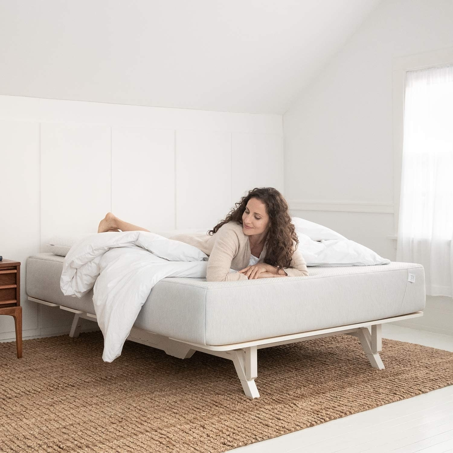 model lounges on Tuft & Needle white adaptive foam mattress on a bed