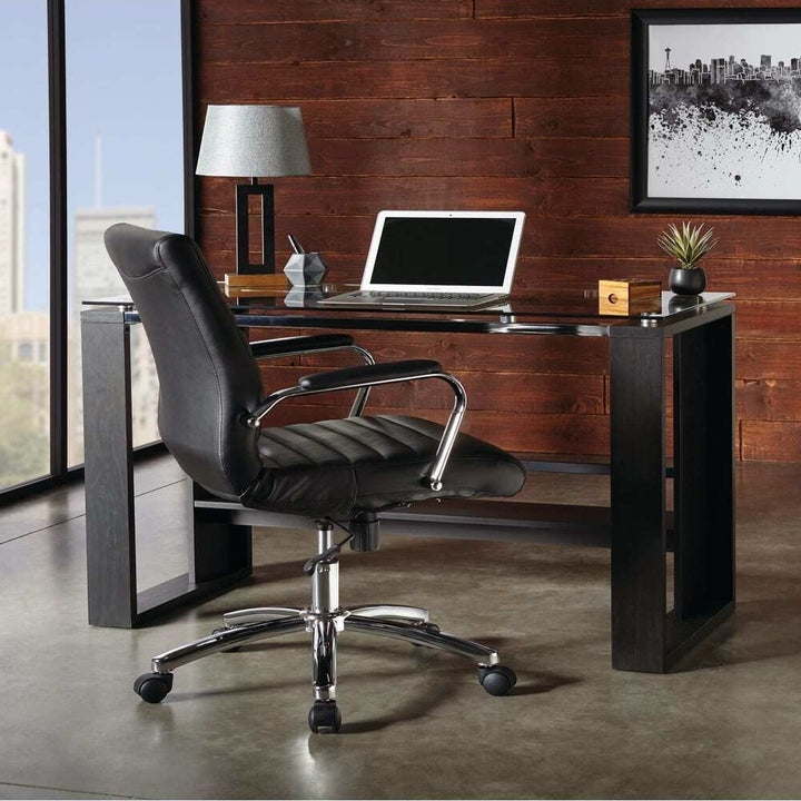Black desk chair next to black desk with laptop on top