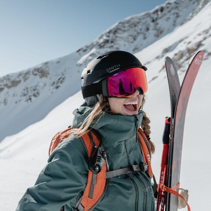 Model wears green hooded jacket while carrying skis on a mountain