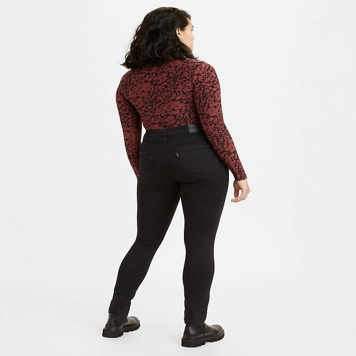 model in black Levi's 721 high-rise skinny jeans with a red leopard-print top and combat boots