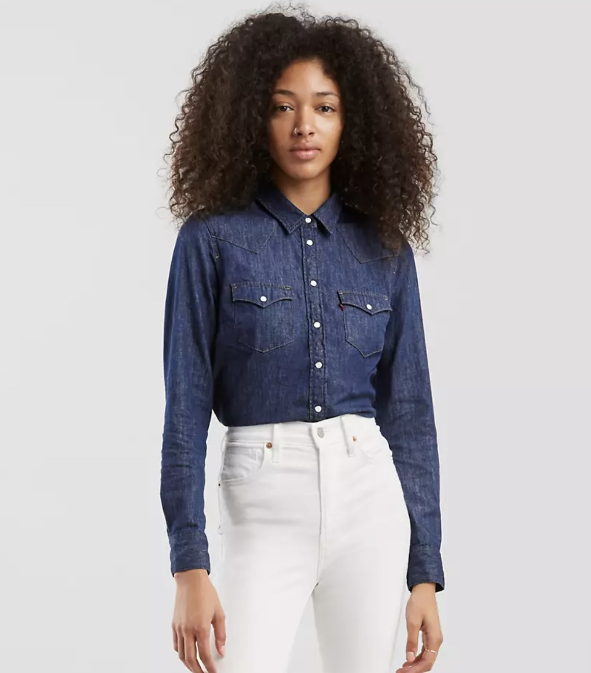 Model is wearing white jeans and a dark blue denim shirt