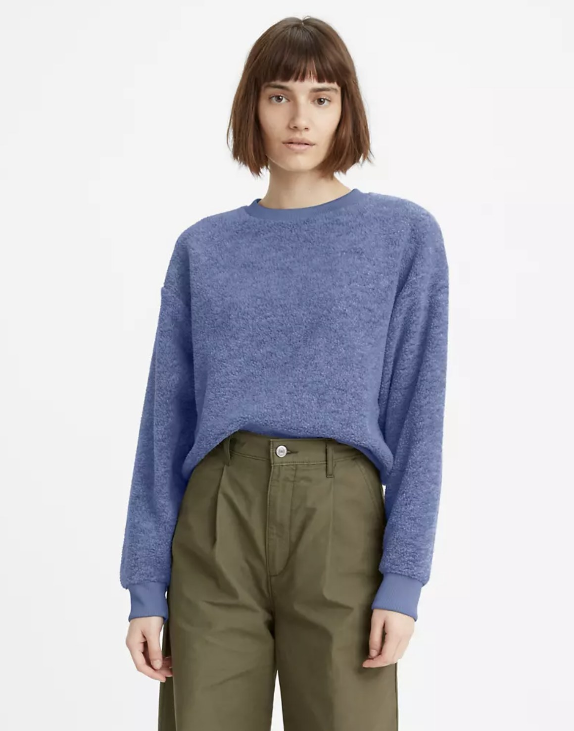 Model is wearing olive pants and a blue crewneck sweatshirt