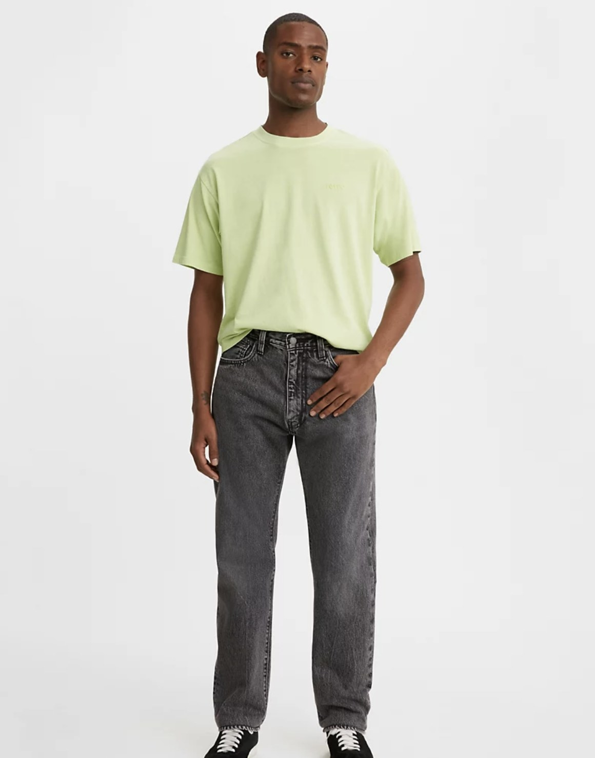 Model is wearing a lime green shirt and black light wash denim jeans