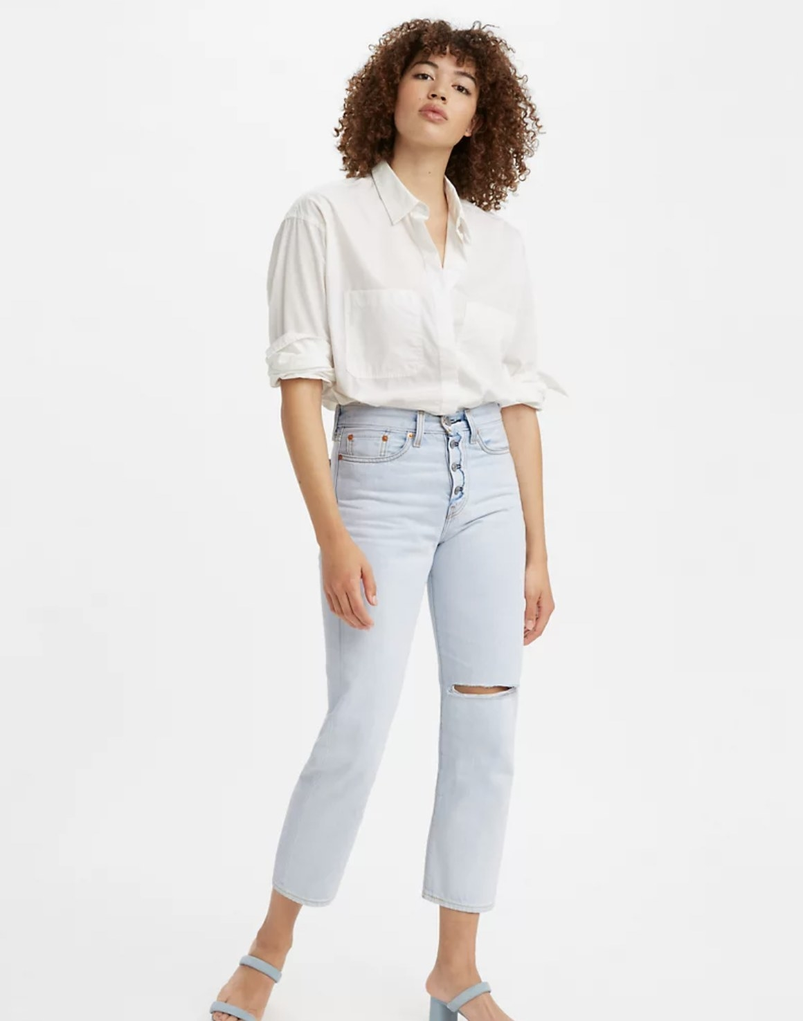 Model is wearing a white top with light straight denim jeans