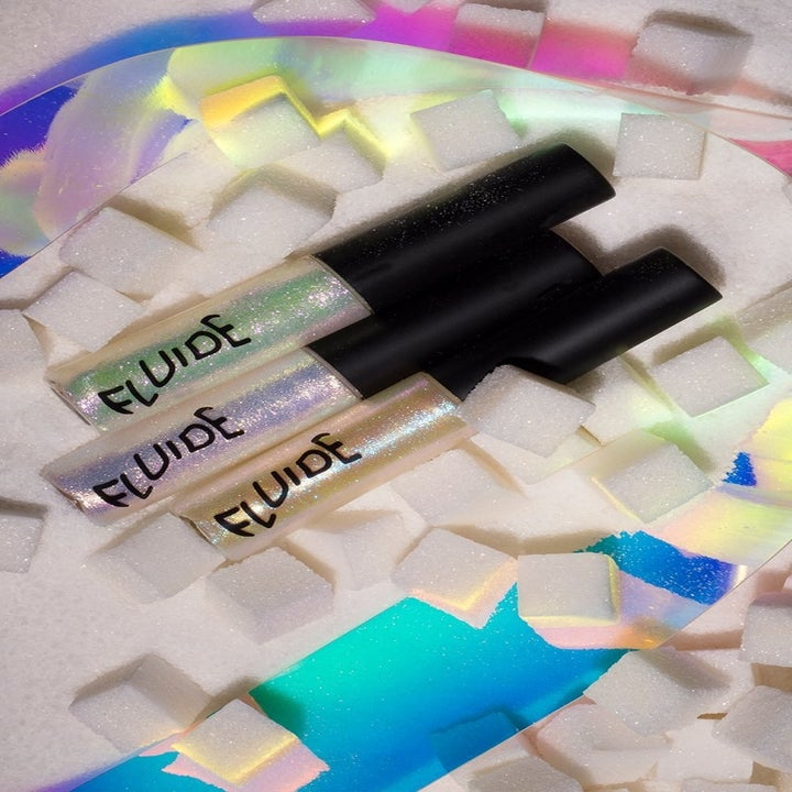 Glittery holographic lip glosses next to sugar cubes