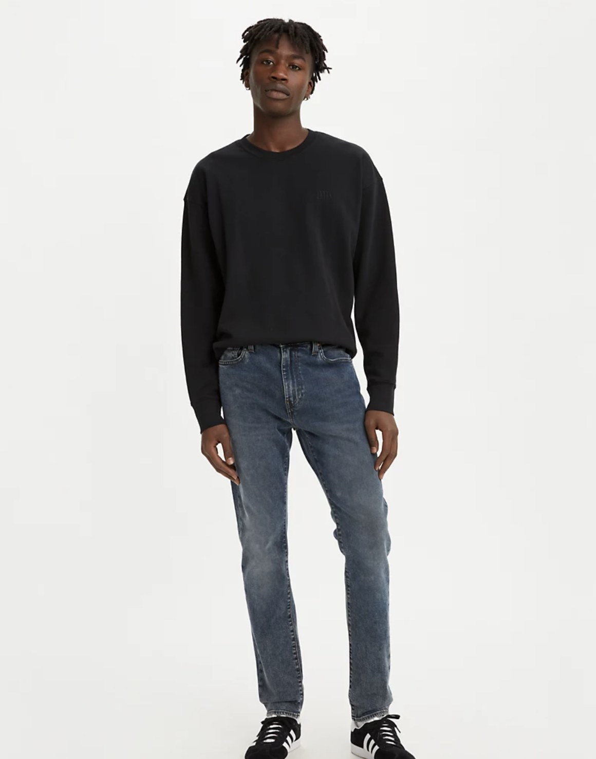 Model is wearing a black sweater and dark denim jeans