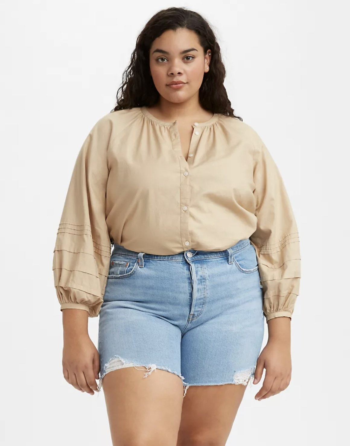 Model is wearing a beige Genevieve top and denim shorts