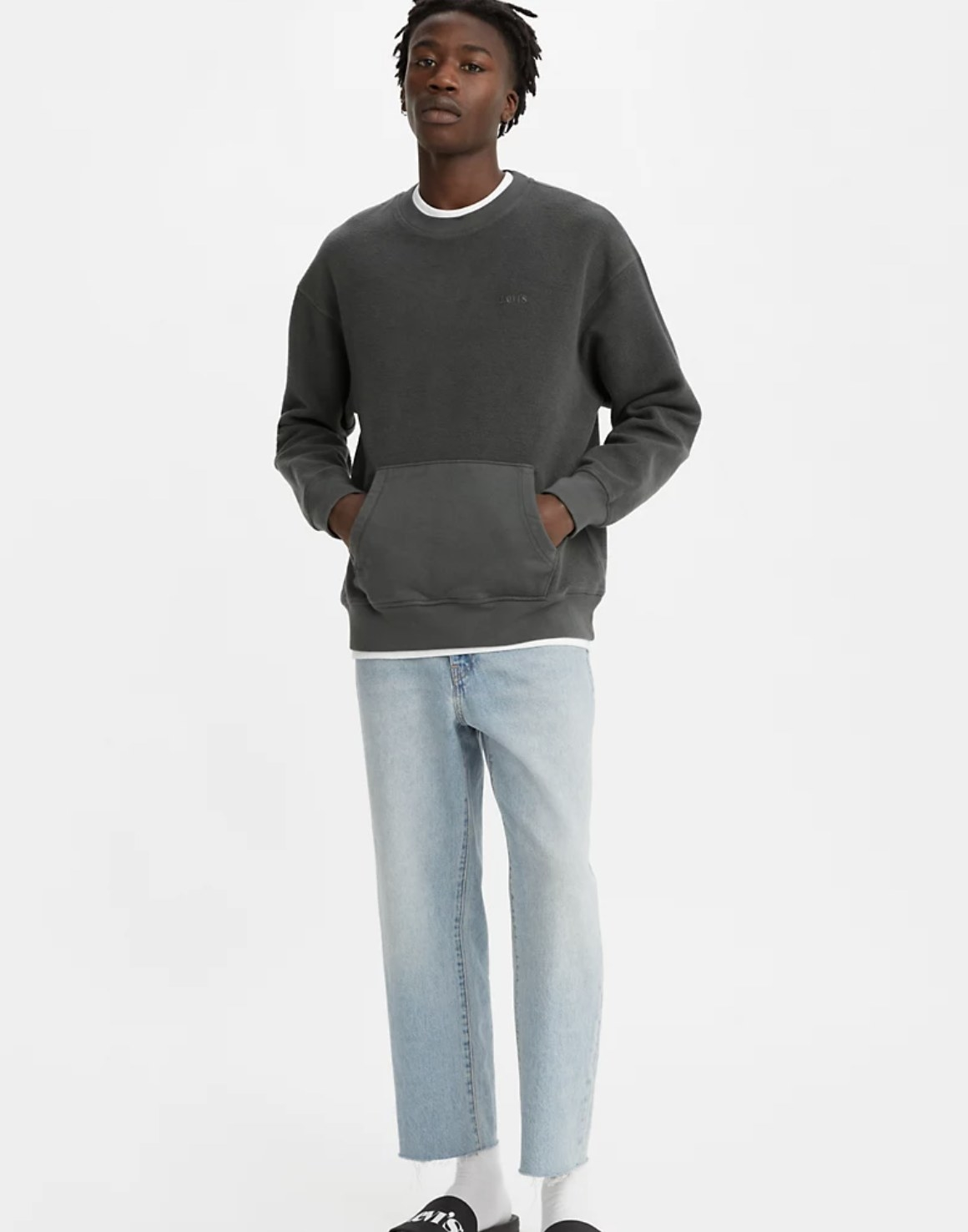 Model is wearing light wash jeans and a dark grey crewneck with a front pocket