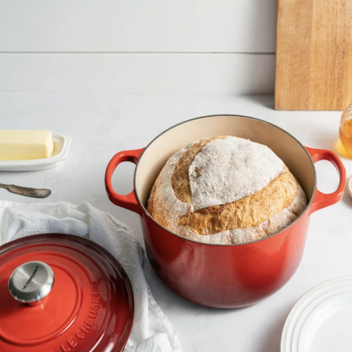 red Le Creuset Cast Iron Round Dutch Oven with baked bread inside
