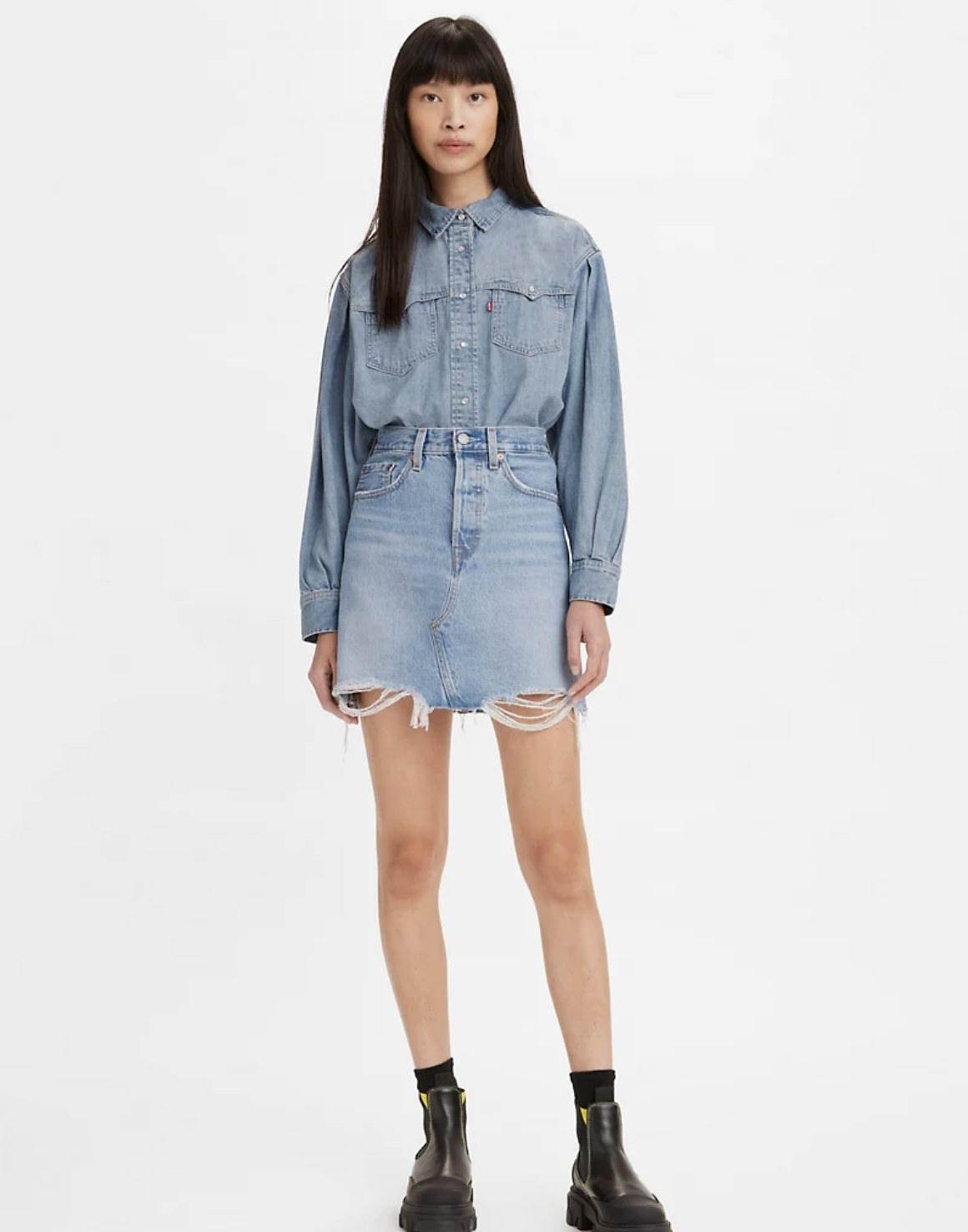 Model is wearing a deconstructed denim skirt with a denim top