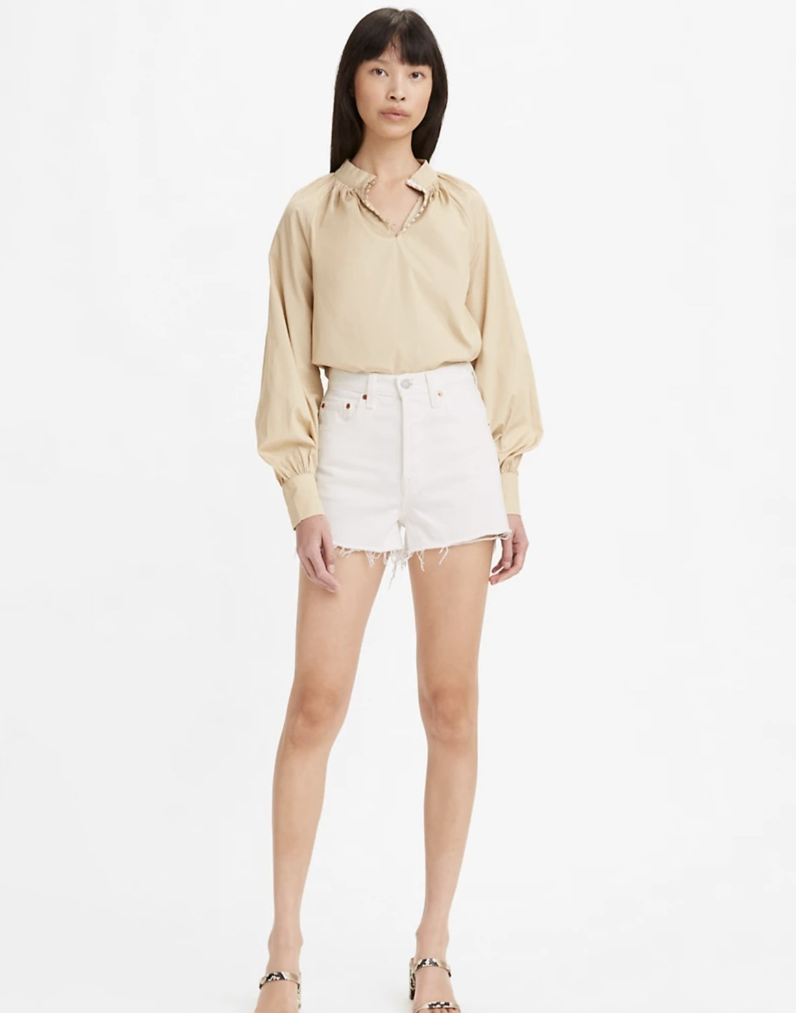Model is wearing a beige top with white shorts