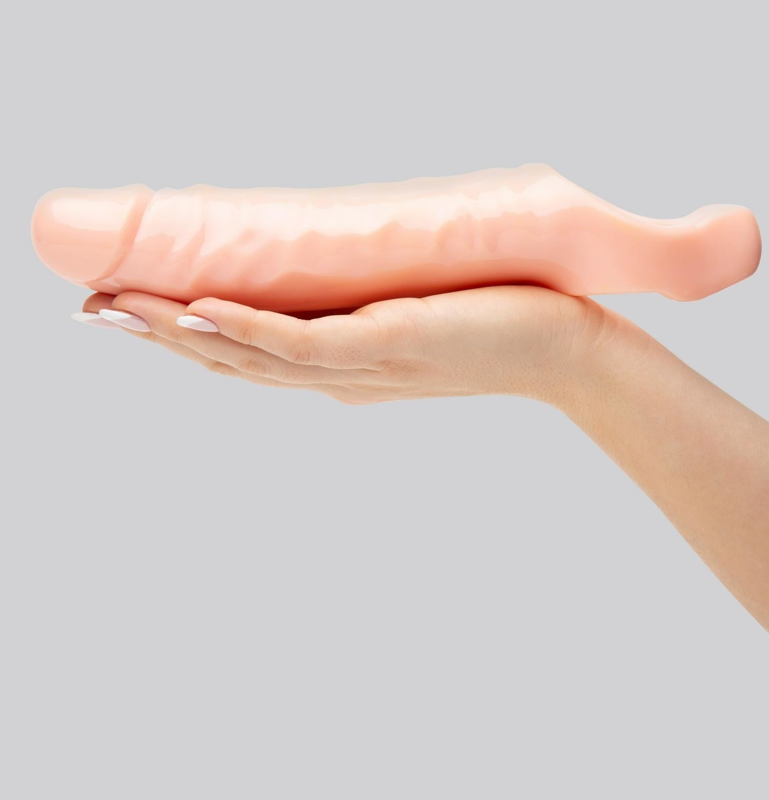 hand holding a penis-like toy with a cavity in it for slipping a penis into