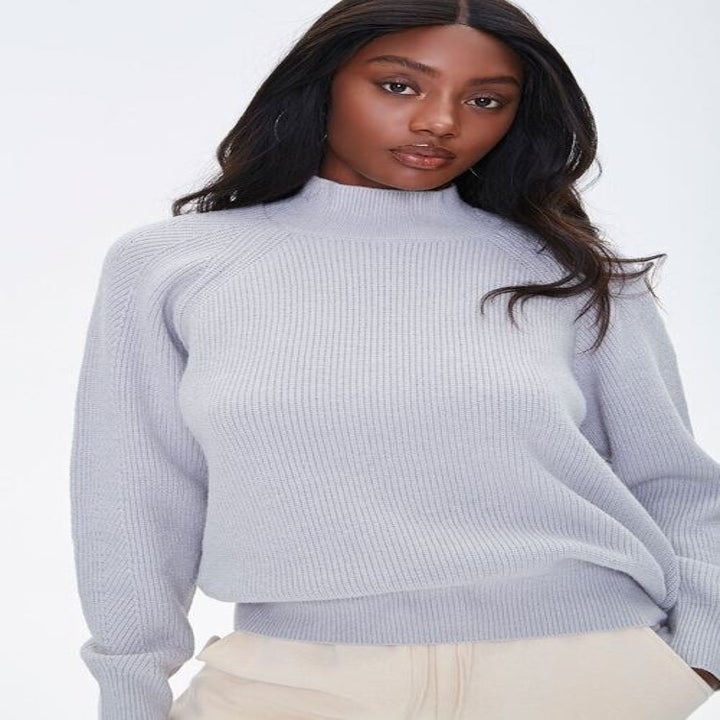 Model wears ribbed pink sweater with white joggers