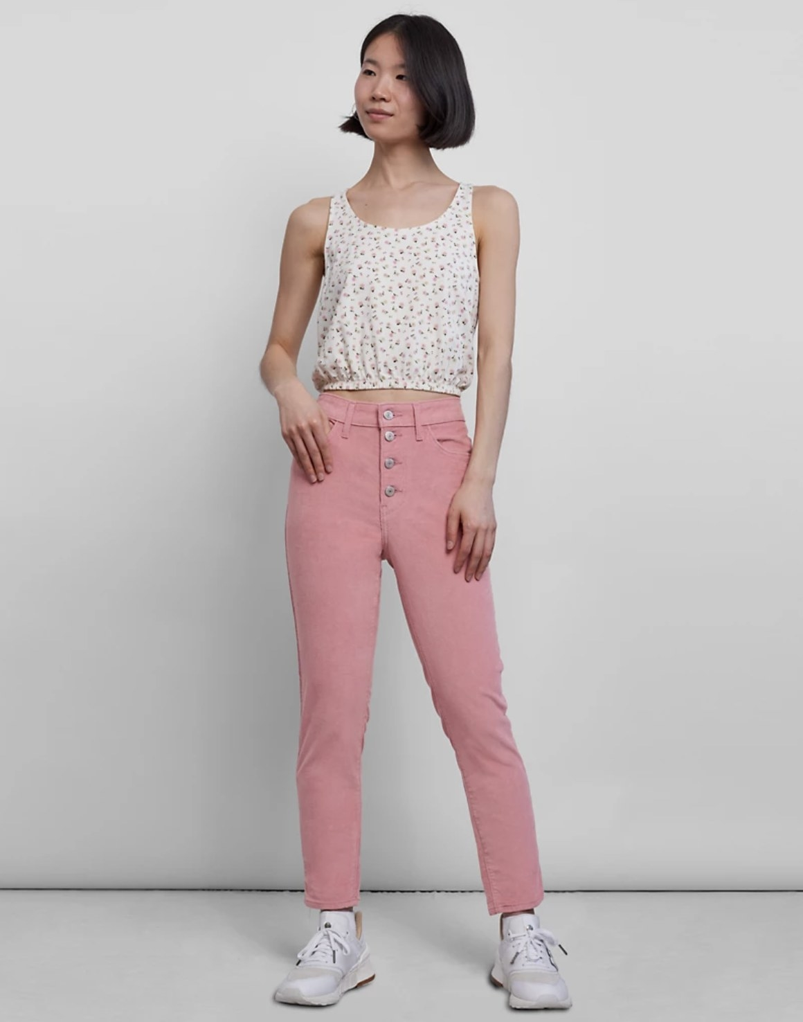 Model is wearing pink corduroy jeans and a tank top