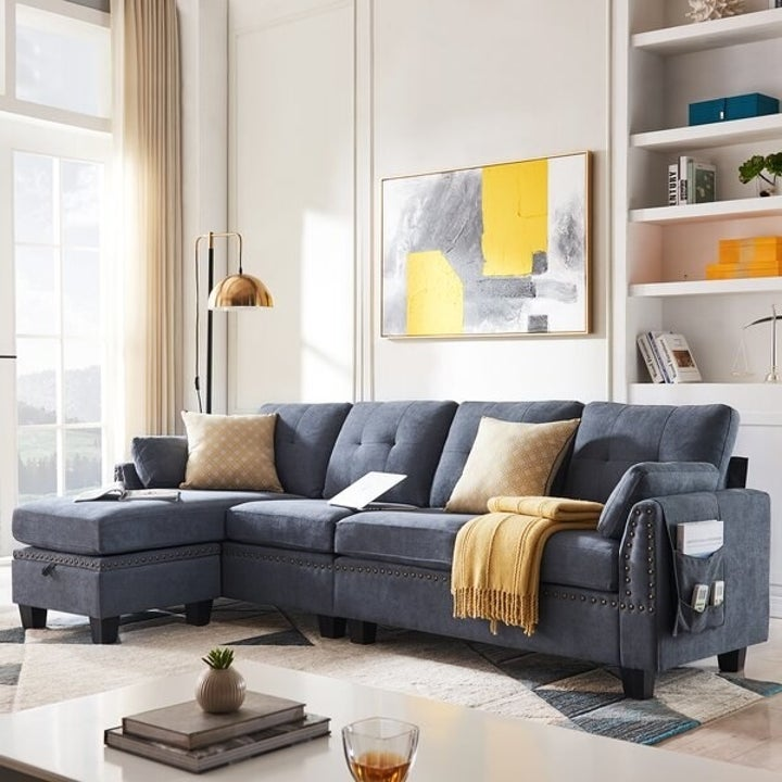Gray reversible sofa and ottoman with yellow pillows on top