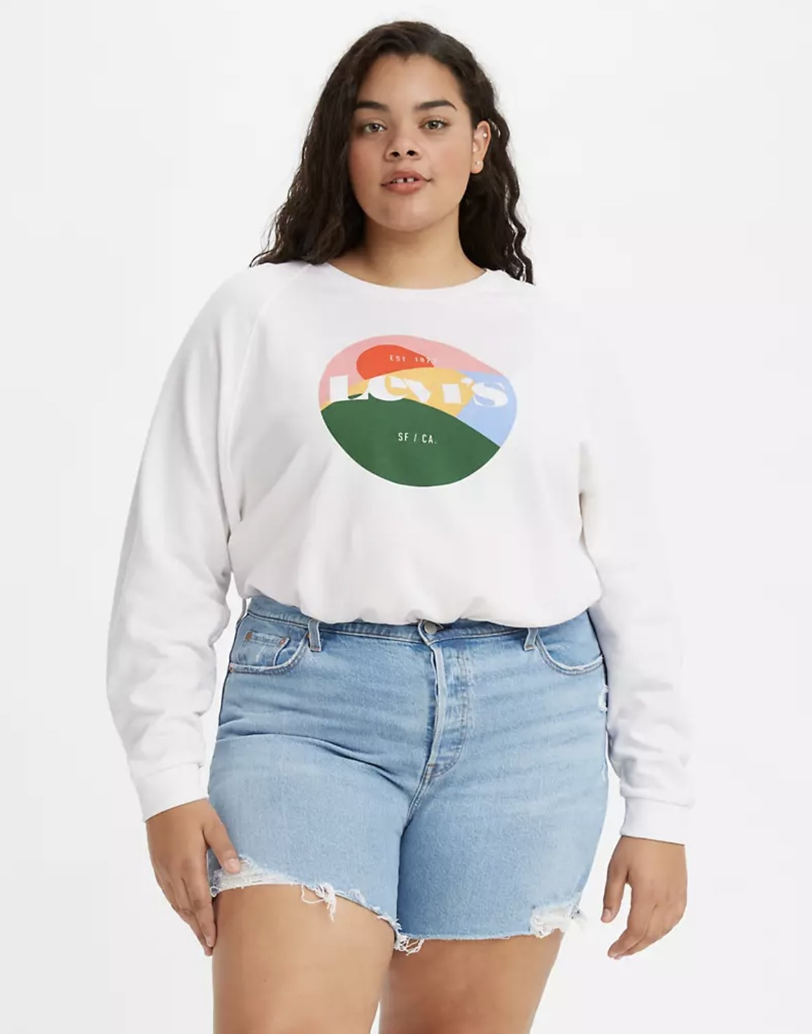 Model is wearing a white sweatshirt and denim shorts