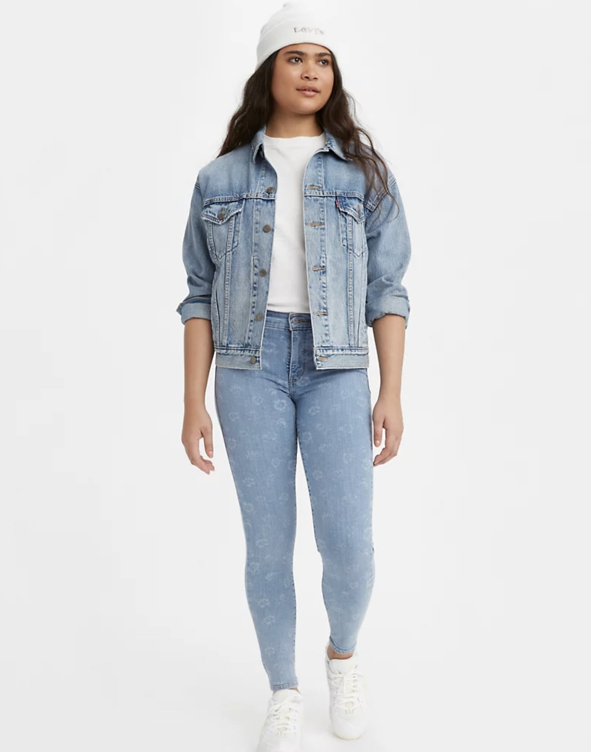 Model is wearing light skinny jeans, a top, and a denim jacket