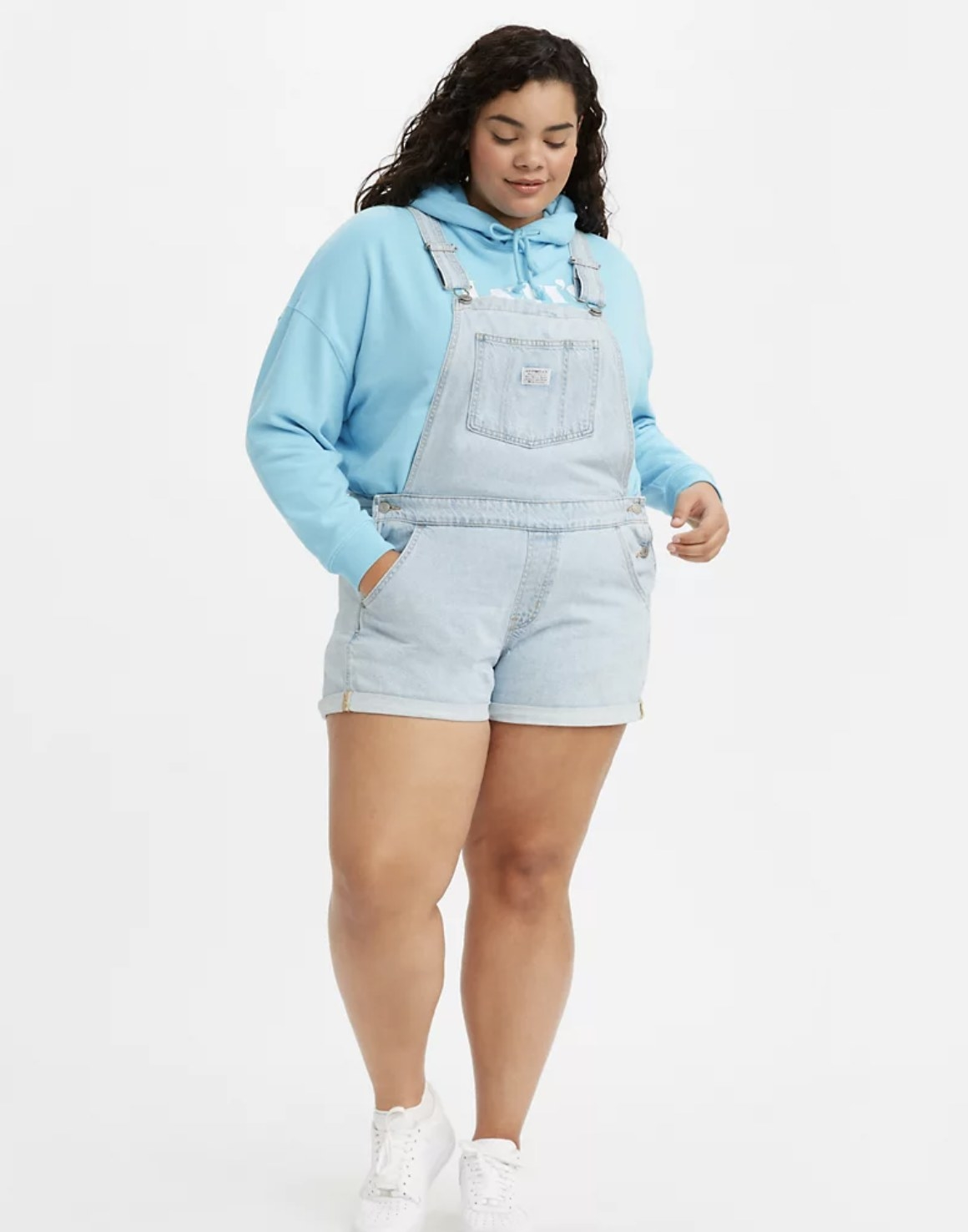 Model is wearing a light blue hoodies and a light wash denim shortall