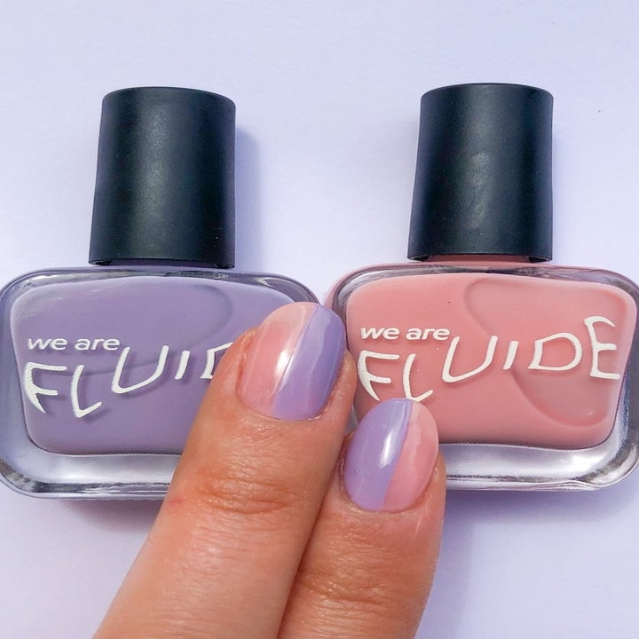 Hand wears two-tone pink and purple nail polish from pastel set