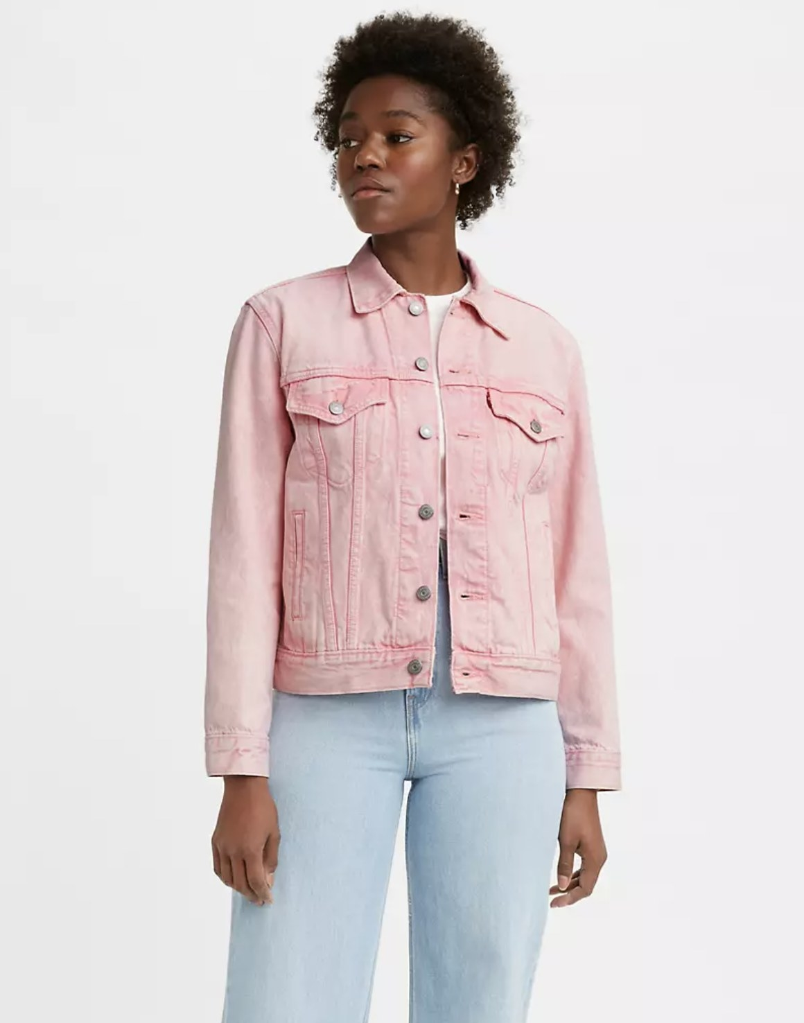 Model is wearing a white top with a pink trucker jacket over it and denim jeans