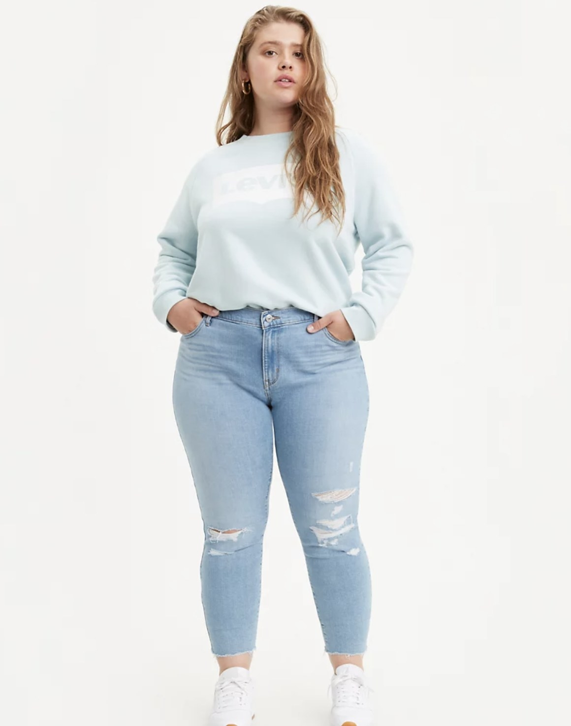 Model is wearing light blue denim jeans with rips and a light blue sweatshirt
