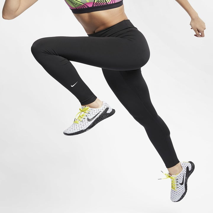 Model wears black workout leggings with white and yellow running sneakers