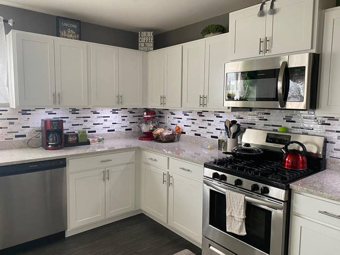 reviewer image of the white marble peel and stick tile used as backsplash in a customer's kitchen