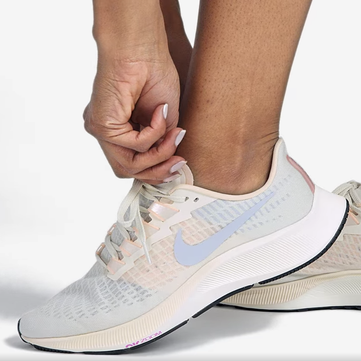 Model laces up light pink, blue, and gray running sneakers