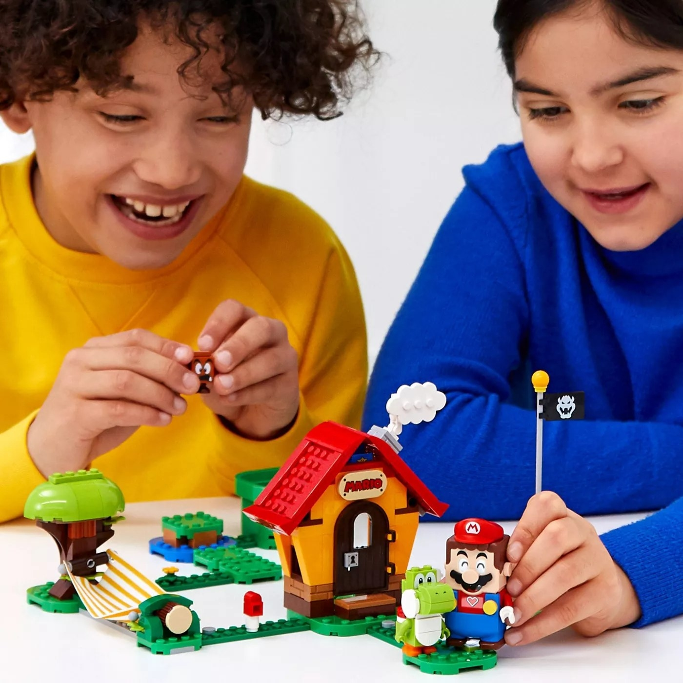 Children playing with a Super Mario LEGO set