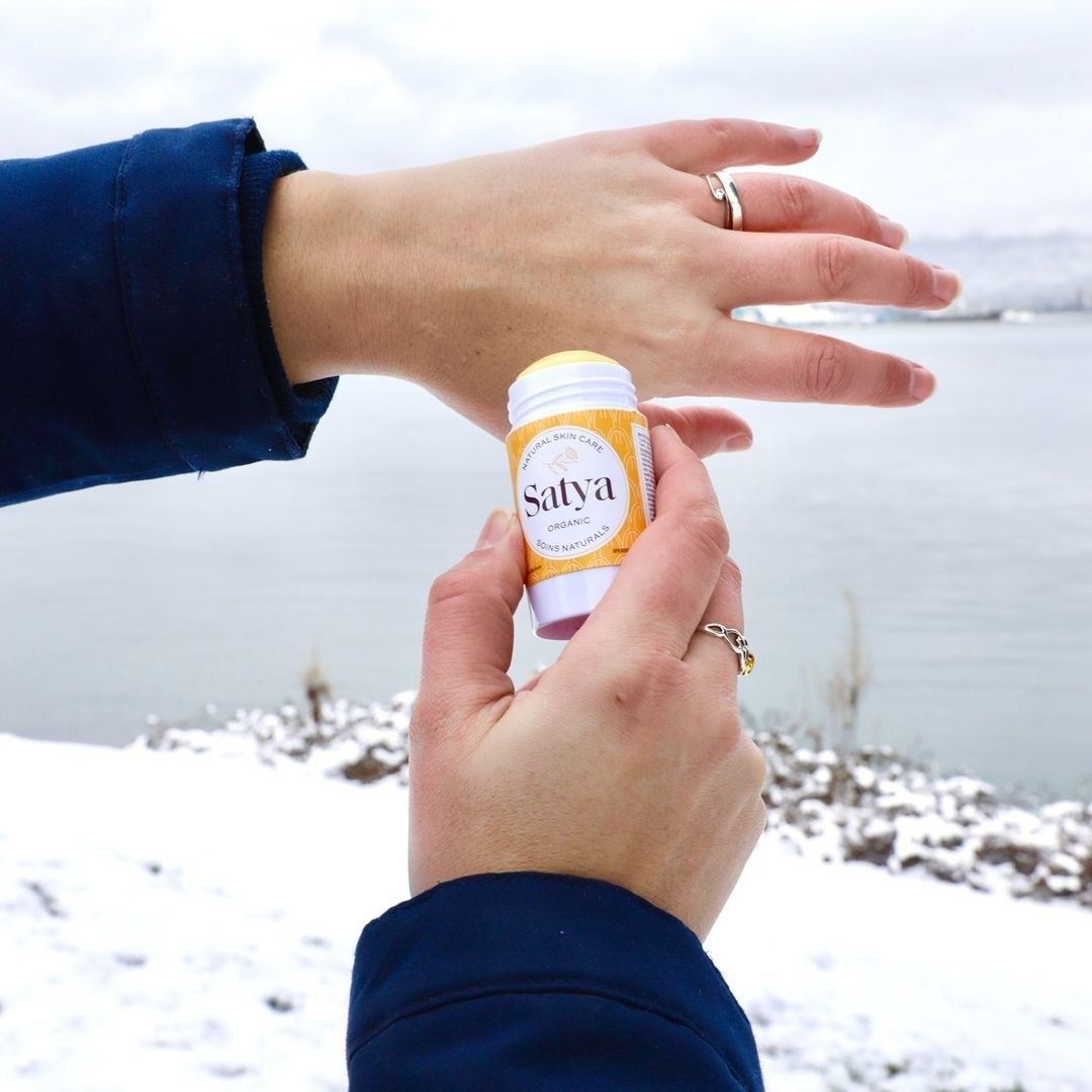 A person applying the lotion stick to their hands in a snowy landscape
