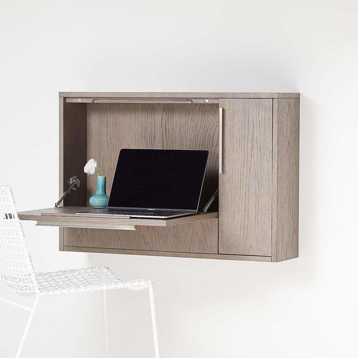 square desk on a wall with part folded down to create a desk