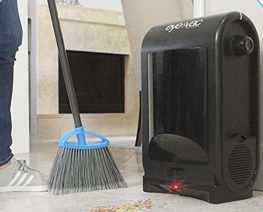 A person sweeps debris underneath the touchless vacuum, which sucks all the debris up