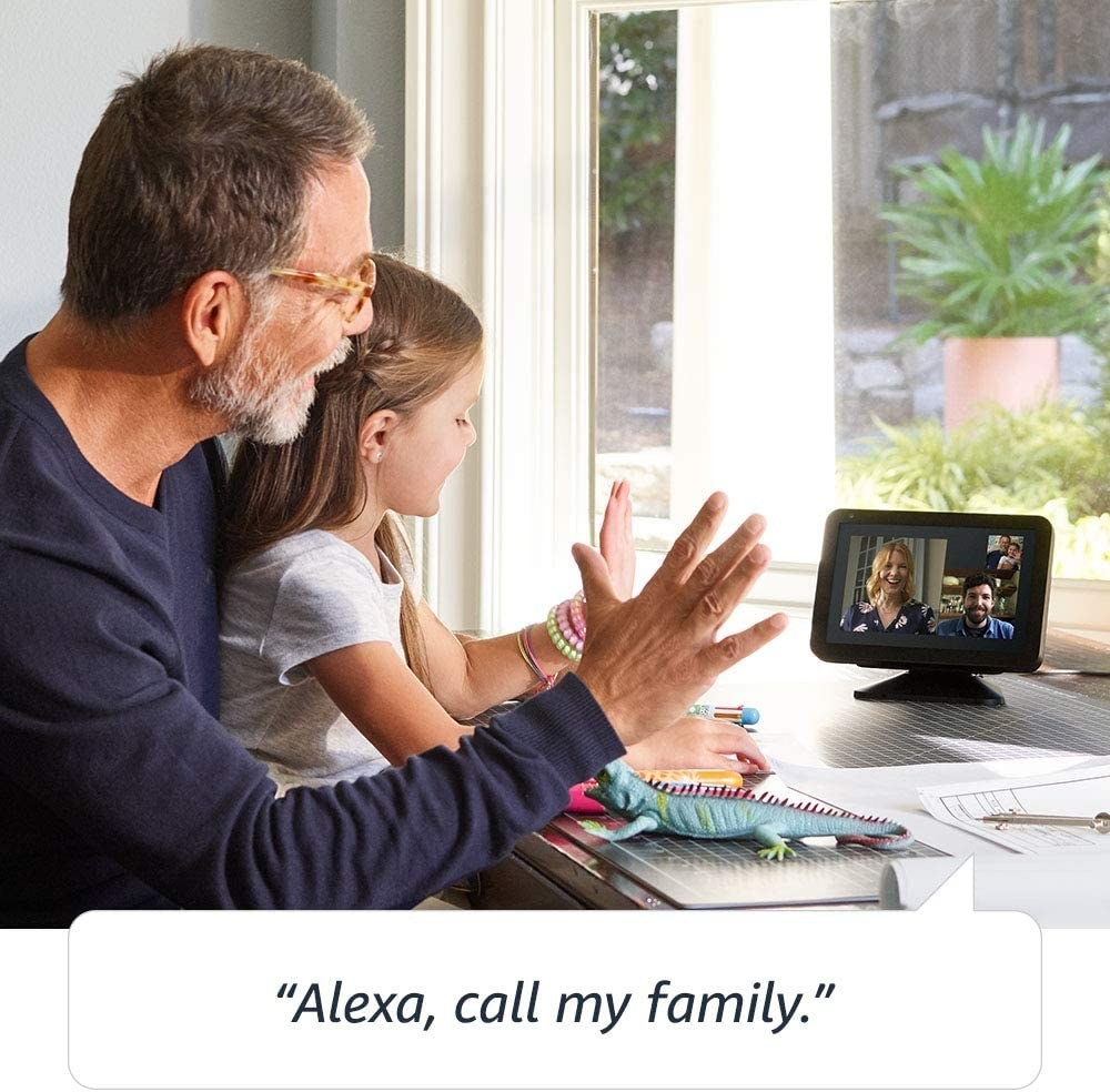 """the rectangle screen with stand a pictures of people with two people waving at it with the words """"Alexa, call my family"""" underneath"""