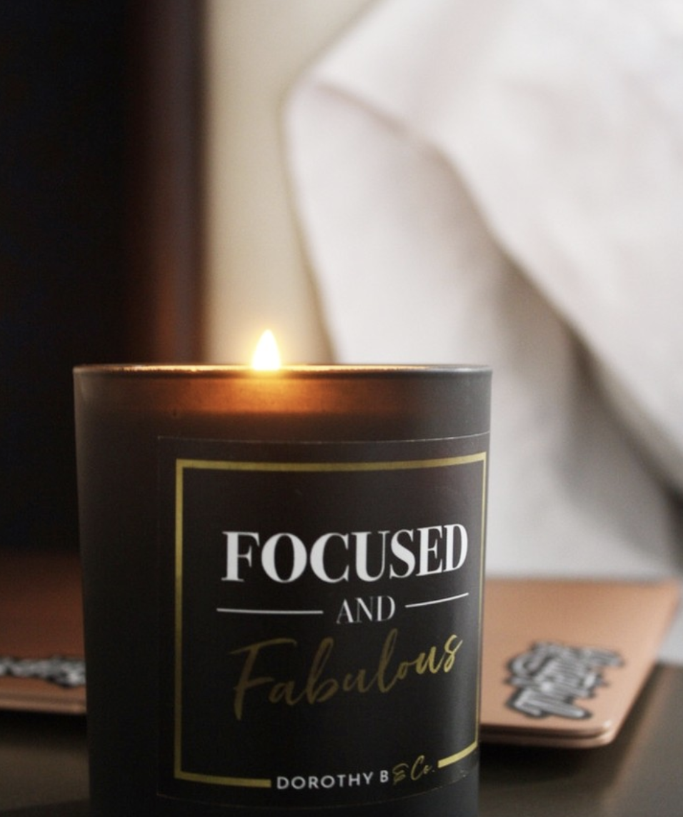 "A lit black candle with white and gold text that says ""focused & fabulous"""